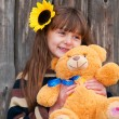 Stock Photo: Girl with teddy bear against wooden fence.