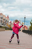 A girl on roller skates coming down the road. — Stock Photo