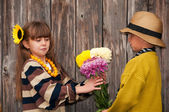 The boy gives a girl flowers. First love. — Stock Photo
