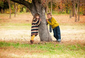 The boy with the girl standing near a tree. — Stok fotoğraf