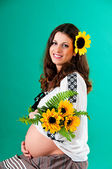 The image of a pregnant woman with sunflower. Ethnic style. — Stock Photo