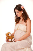 The image of a pregnant woman sitting with a teddy bear in her a — Stock Photo