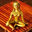 Statuette of deep meditation in sunlight - Stock Photo