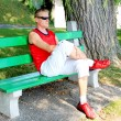 Handsome young man sitting on a park bench — Stock Photo #9420324