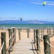 Wooden stairs and kite surfers on beach Riumar Spain — Stock Photo #9532420