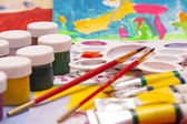 Paints and brushes on the background of children's drawings — Stok fotoğraf