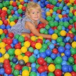 Stock Photo: Happy girl playing in balls.