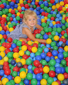 Happy girl playing in balls. — Stock Photo