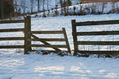 Broken fence in the snow at sunset — Stock Photo