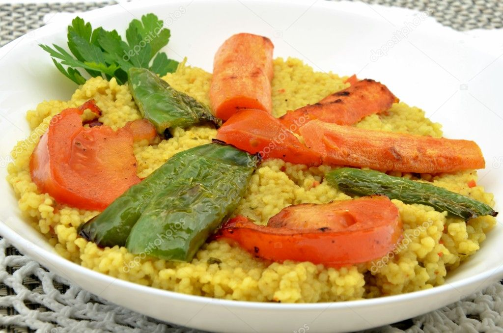 Couscous with vegetables served in a bowl on a tablecloth — Stock Photo #9970341