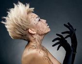 Beautiful girl in black gloves, with a creative hairdress, and b — Stock Photo