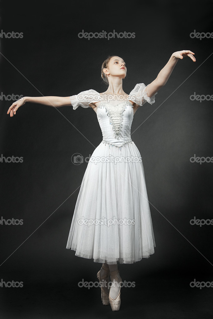 Beautiful dancer posing in a white dress, on studio background. Looks upwards. — Photo #8560028