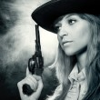 Beautiful girl in hat, with a revolver - Stock Photo