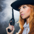 The beautiful girl in hat, with a revolver. - Stock Photo