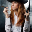 The beautiful girl in hat, with a revolver — Stock Photo #8612493