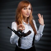 Girl with red hair gives a revolver — Stock Photo