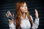 Beautiful girl with red hair gives a revolver — Stock Photo