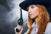 The beautiful girl in hat, with a revolver. — Stock Photo