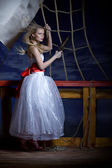 Beautiful girl in a white dress on a deck of the sailing ship. — Stock Photo