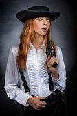 Beautiful girl with red hair plays a revolver — Stock Photo