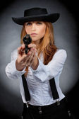 Beautiful girl in hat, red hair, with revolver in hands. — Stock Photo