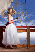 Beautiful girl in white dress on deck of the sailing ship — Stock Photo