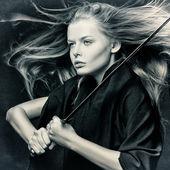 Close-up van mooi meisje met zwaard. — Stockfoto