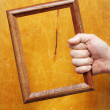 Man's hand holding a wooden frame — Stock Photo