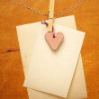 Vintage photos and red heart hanging on the clothesline - Stock Photo