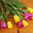 Yellow and pink tulips on wooden board — Stock Photo