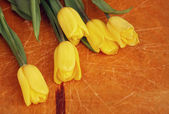 Yellow tulips on wooden table — Stock Photo