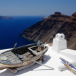 Boat on the white roof. Santorini, Greece - Stock Photo