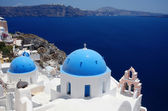 Blue domes and their bell tower in Santorini — Stock Photo