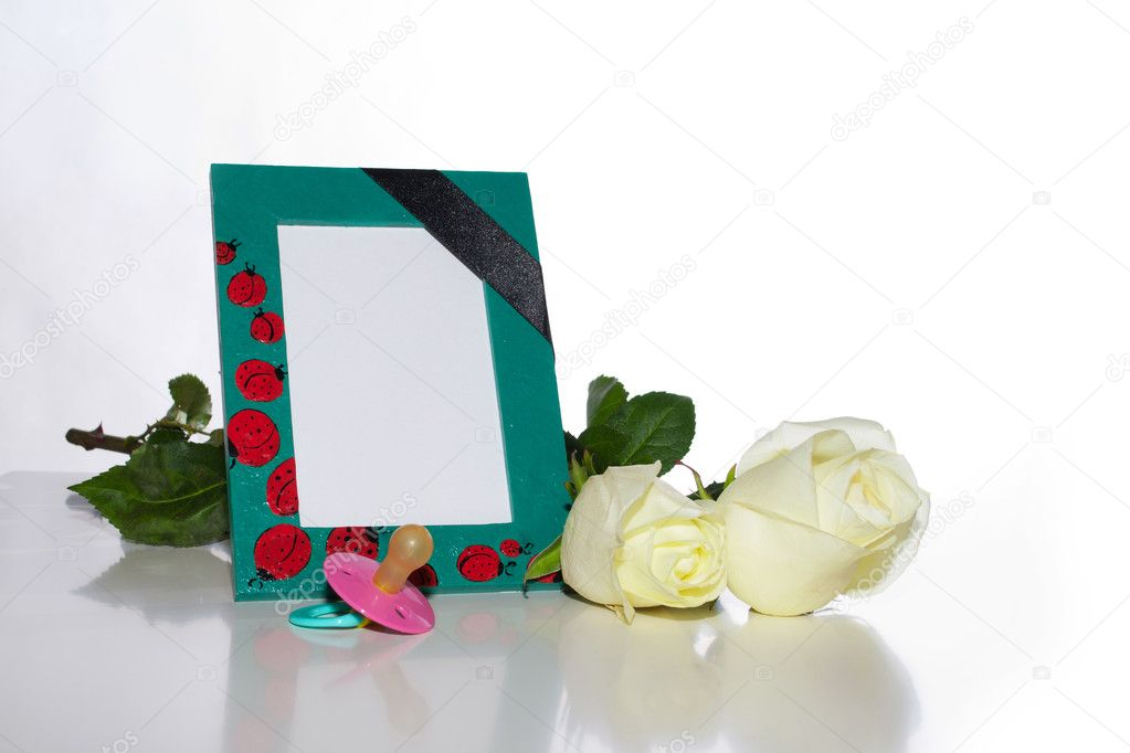 The nursery a photo frame with a mourning black tape, white roses and a children's dummy on a light background — Stock Photo #9715323