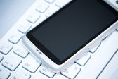 Smart phone on laptop — Stock Photo