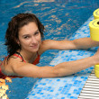 The girl is engaged aqua aerobics with dumbbells - Stock Photo