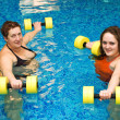 Two womam in water with dumbbells — Stock Photo