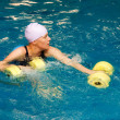 Girl in water with dumbbels — Stock Photo