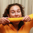 Young funny girl eating corn — Stock Photo