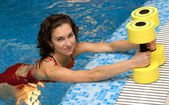 The girl is engaged aqua aerobics with dumbbells — Stock Photo
