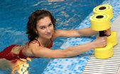 The girl is engaged aqua aerobics with dumbbells — Stock Photo
