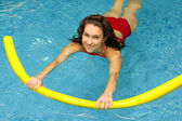 Young woman is swimming with noodle — Stock Photo