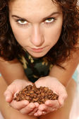 Girl shows coffee grains in hands — Stock Photo