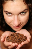 The girl holds coffee grains in hands — Stock Photo