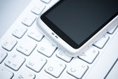 Smart phone over white keyboard — Stock Photo