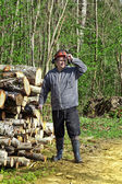 Lumberjack near a pile of logs — Stock Photo