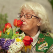 Grandmother with flowers — Stock Photo