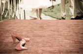 Red bridal shoes and barefoot bride in the background — Stock Photo