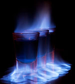 Burning drink in shot glass on a table — Stock Photo