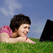 Young casual woman working on laptop outdoors — Stock Photo #8827125